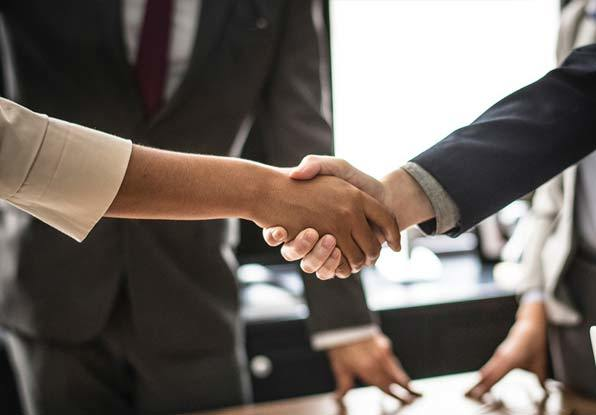 Image of partners shaking hands to a deal